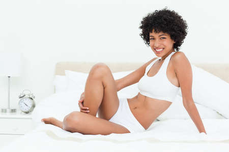 frizzy: Smiling frizzy haired woman on her bed in a bright bedroom