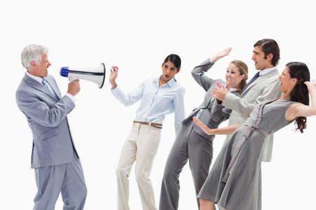 personas comunicandose: Hombre que grita en un megáfono en la gente de negocios aturdidos contra el fondo blanco