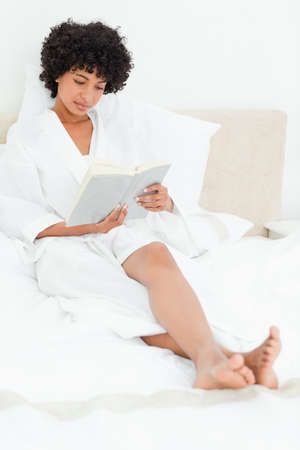 feet crossed: Frizzy haired woman in a dressing gown reading a book