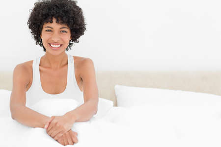 frizzy: Portrait of a frizzy woman smiling in her white bed LANG_EVOIMAGES