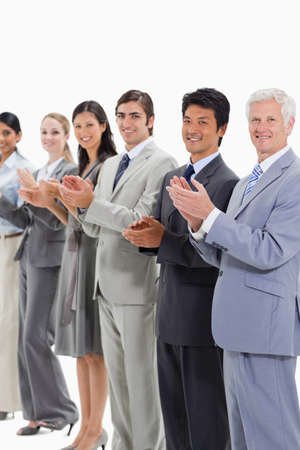 applauding: Multicultural smiling business people applauding and posing against white background