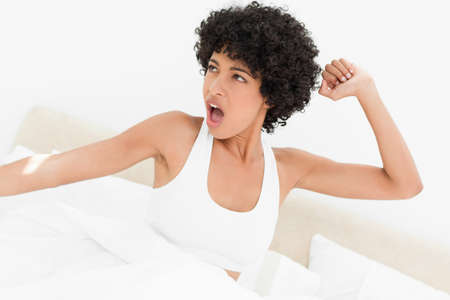 frizzy: Attractive frizzy haired woman yawning and stretching her arms in her bed