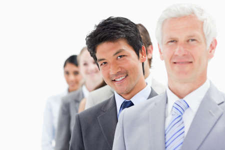 single line: Close-up of a single line of smiling business people with focus on the second person against white background LANG_EVOIMAGES