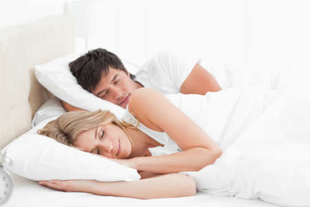 gente durmiendo: A man and woman with an arm under a pillow, sleeping in the bed together.