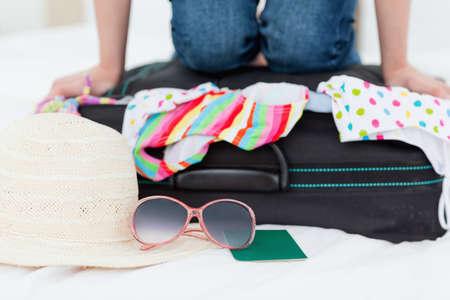 mujer arrodillada: Una mujer de rodillas en su maleta, tratando de hacer que todo encaje en ella.