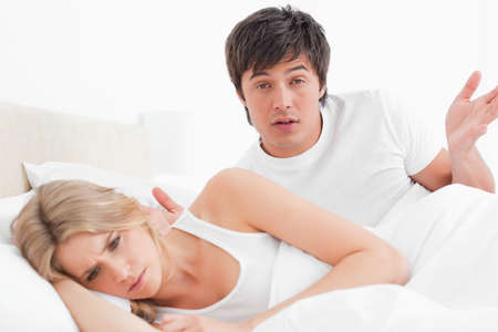 obudził: A man and woman are arguing in bed with the woman turned away from the man and the man looking confused.