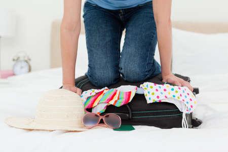mujer rodillas: Una mujer de rodillas en su maleta en un intento de hacer everythin encajar. LANG_EVOIMAGES