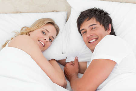 facing each other: A man and woman smiling as they look upwards while facing each other in bed. LANG_EVOIMAGES