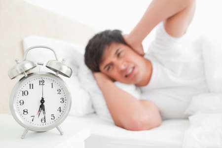 awoken: Focus on the alarm clock as it rings loudly making the man block his ears. LANG_EVOIMAGES