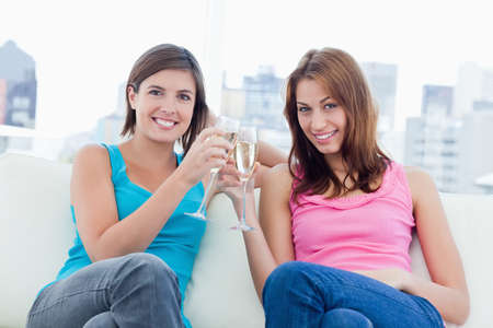 clinking: Two young smiling women sitting on a sofa while clinking glasses of champagne