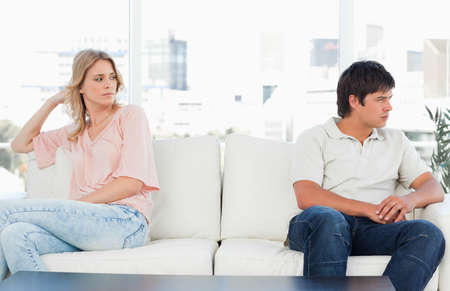 agitated: A man looking angry turned the opposite way to the woman at the other end of the couch looking upset. LANG_EVOIMAGES