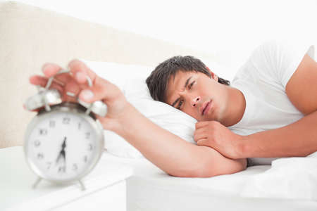 awoken: A man turning off his alarm clock with his hand looking straight ahead.