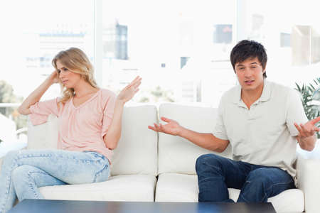 agitated: The woman has her hand up in a sign of not interested, while the man has his hands up in a gesture of confusion as of what to do.