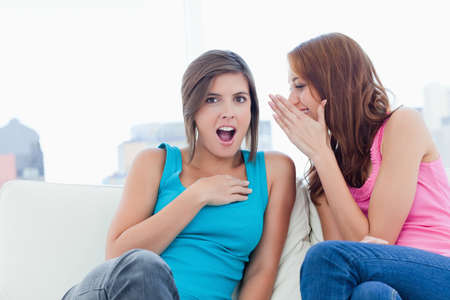 told: Teenager being told a surprising secret by her friend