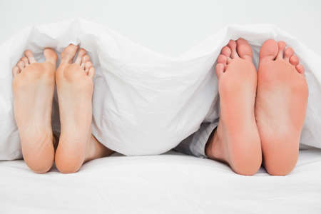 straight up: Two pairs of feet beside each other pointing straight up in the bed. LANG_EVOIMAGES