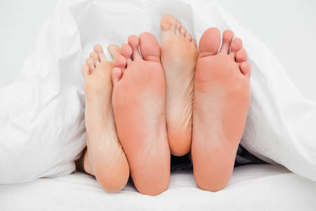 pairs: Two pairs of feet in the bed in between each other.
