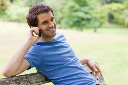 call of nature: Young relaxed man sitting on a bench while calling with his mobile phone