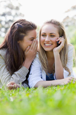 told: Young smiling woman calling with her cellphone while lying and being told a secret