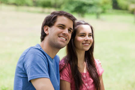 countryside loving: Young smiling man placing his arm around his girlfriend in a public garden LANG_EVOIMAGES