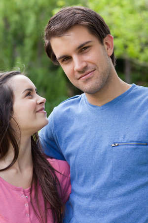 countryside loving: Young lovely couple showing their happiness while holding each other in a parkland