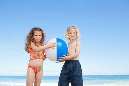 siblings: Young siblings with their beach ball standing on the beach