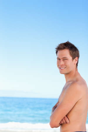 arms folded: Side view of a young man with his arms folded standing on the beach