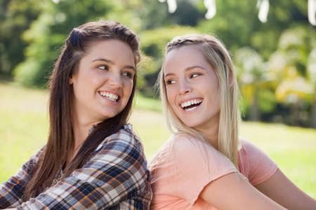 each: Young women smiling to each other while standing back to back in the countryside