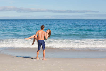 carried: Young woman carried by her boyfriend on the beach LANG_EVOIMAGES