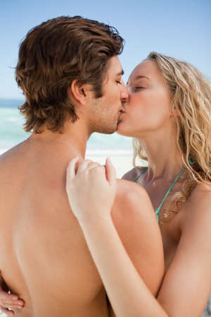 passionately: Young cute couple standing on the beach while passionately kissing each other