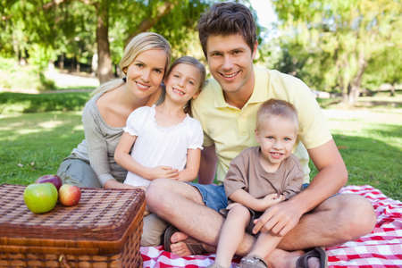 family: A joyful family sitting on the blanket of their picnic while looking straight ahead LANG_EVOIMAGES