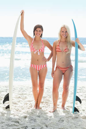 standing together: Two women in bikinis smiling happily as they stand next to perched surfboards on the beach