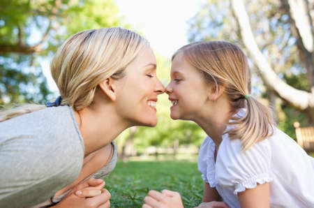 rubbing noses: A smiling mother and daughter rub noses together in the park LANG_EVOIMAGES