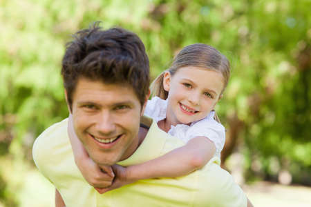 piggyback: A smiling father gives his daughter a piggyback