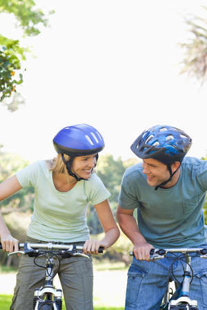 get ready: Smiling couple looking at each other with helmets on as they get ready to cycle
