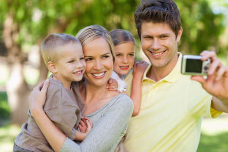 close together: A smiling family pushes close together to take a photo LANG_EVOIMAGES