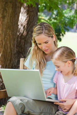 mother on bench: Mother and daughter together with laptop on a park bench LANG_EVOIMAGES