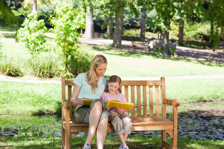 mother on bench: A mother and daughter read together while they sit on the park bench