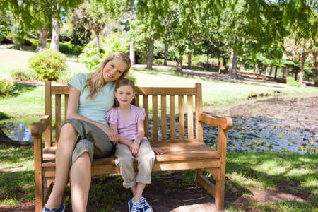 head tilted: A mother with her head tilted slightly smiles with her daughter as they sit on the bench