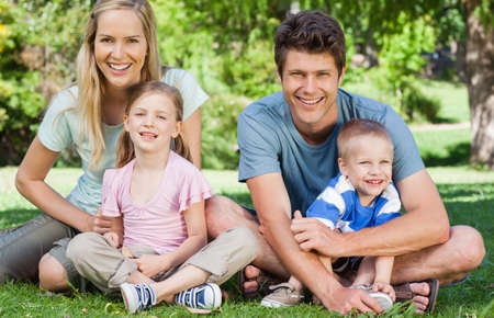 held down: A smiling family sits down on the grass together as the kids are held by their parents LANG_EVOIMAGES