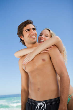 novio: Young attractive woman embracing her cute boyfriend on the beach LANG_EVOIMAGES