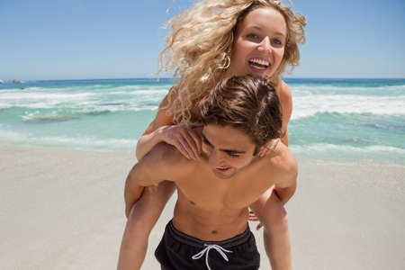 piggyback: Young smiling woman being given a piggy-back by her boyfriend on the beach