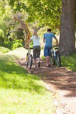 wheeling: Back view of young couple wheeling their bikes through a park
