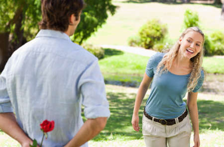 gift behind back: Young man about to give his girlfriend a rose in the park