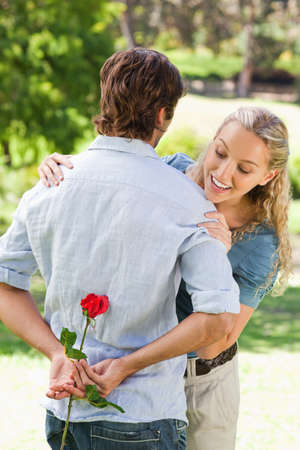 gift behind back: Young woman looking behind her boyfriends back to find a rose
