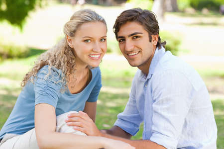 male bonding: Side view of a happy young couple sitting on the grass LANG_EVOIMAGES