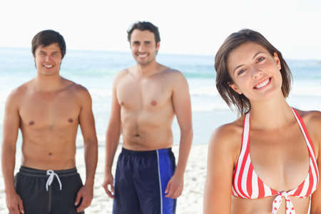 head tilted: Woman wearing a bikini smiling with her head tilted as her two friends stand behind her in swimsuits on the beach LANG_EVOIMAGES