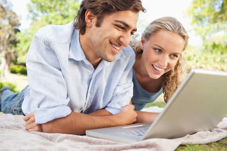 technology: Young couple lying on the lawn with their laptop