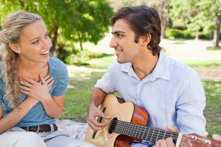 impress: Young male playing the guitar to impress his girlfriend LANG_EVOIMAGES