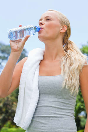 sportswoman: Young sportswoman drinking a bottle of water LANG_EVOIMAGES