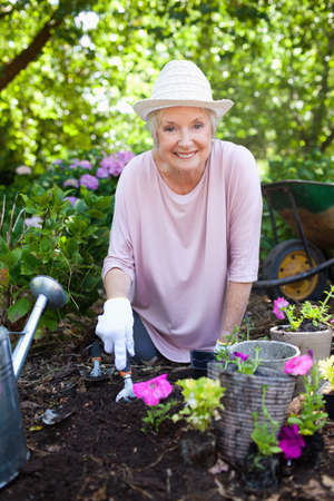 70s adult: Woman smiling happily while planting pink flowers in her garden